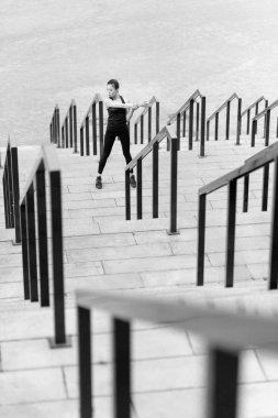 Sportswoman training on stadium stairs