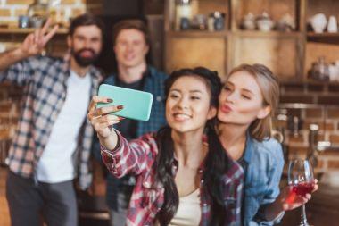Girls taking selfie with boys