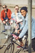 Fotografie teenagers with shopping cart and bicycle
