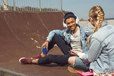Hipster couple listening music with headphones and siiting in skateboard park, teenagers having fun concept stock vector