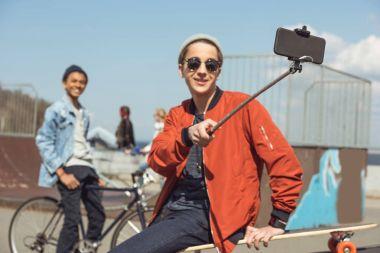 Teenager taking selfie on smartphone in skateboard park, hipster selfie concept stock vector