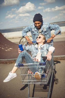 Teenagers having fun with shopping cart