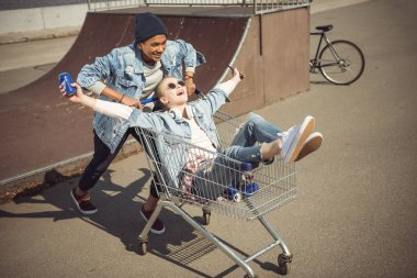Teenagers having fun with shopping cart