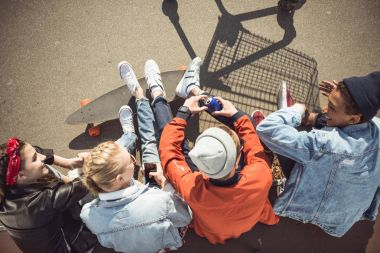 Overhead view of teenagers group sitting together and talking at skatepark stock vector