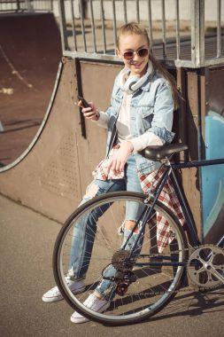 Girl with bike using smartphone