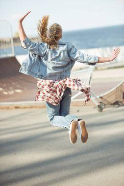 girl jumping at skateboard park