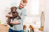Photo father holding puppy