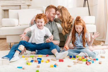 Beautiful redhead family playing with constructor on floor at home, big family portrait concept stock vector