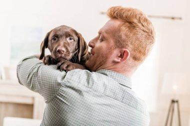 man holding puppy