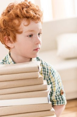 little boy and pile of books