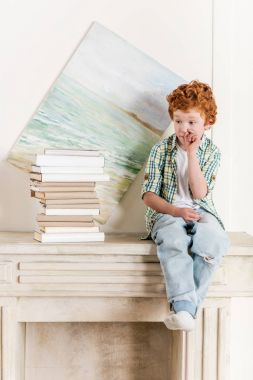 Pensive little boy sitting on fireplace near pile of books stock vector