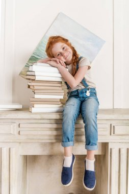 little girl and pile of books