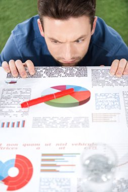 businessman looking at documents with charts and diagrams
