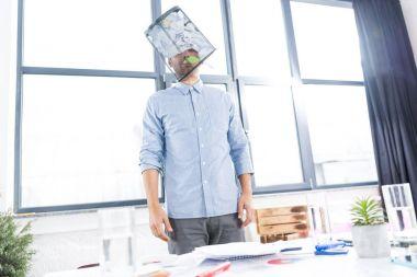 businessman with trash bucket on head