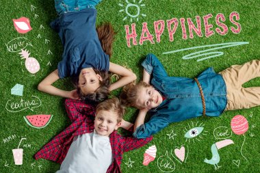 Happy three friends lying on grass