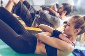 Fotografie Sportliche junge Menschen trainieren im Fitness-Studio