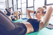 Fotografie Athletic young people exercising in gym