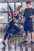Photo sportive woman with trx equipment