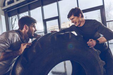men pulling tire together