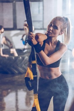 sportive woman with trx equipment
