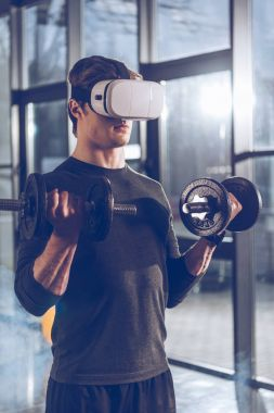 Side view of man in virtual reality headset exercising with dumbbells in gym stock vector