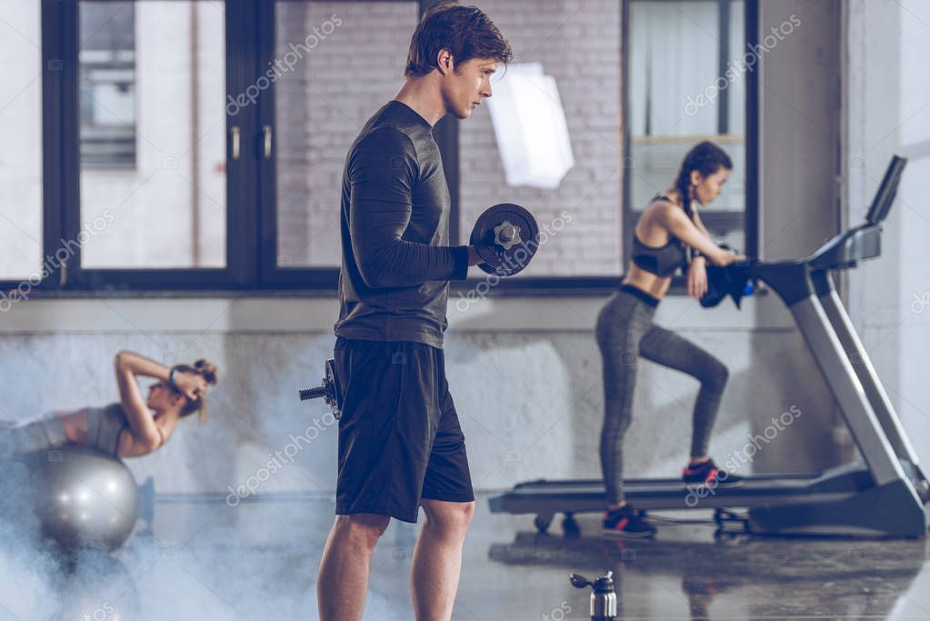 sportsman exercising with dumbbell