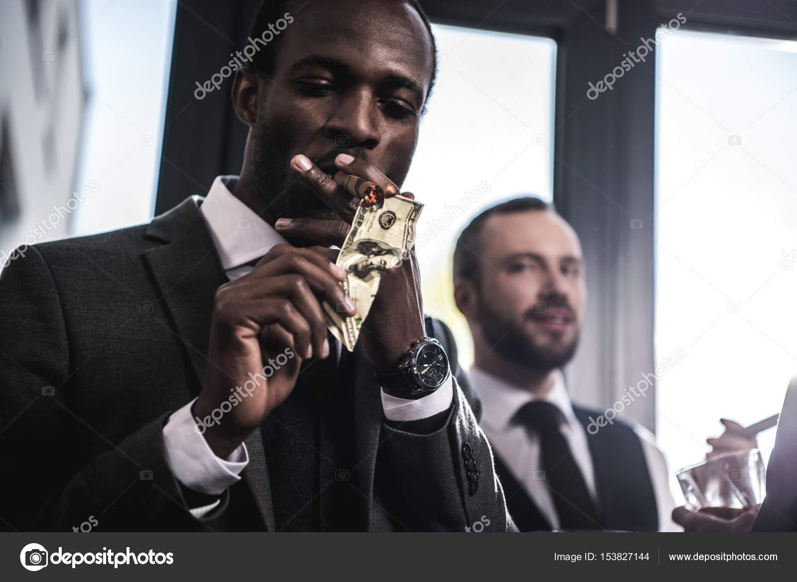 Vertrouwen zakenman verlichting sigaar met dollar biljet binnenshuis ...