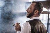 Boční pohled na usmívající se jistý muž kouření doutníku uvnitř