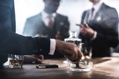 cropped view of businessman extinguishing cigar in glass ashtray
