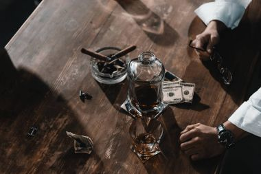 dollar banknotes, whiskey and cigars in ashtray on wooden table
