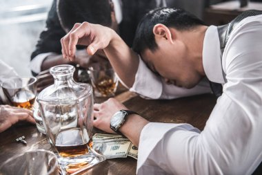 drunk colleagues sleeping at table while spending time together after work