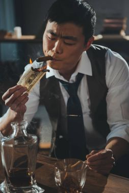 confident asian businessman smoking cigar and burning dollar banknote