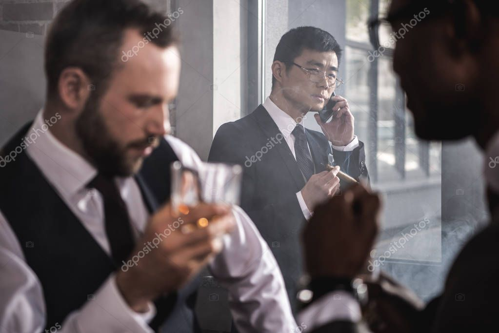 Serious asian businessman smoking cigar and talking on smartphone while colleagues drinking whisky, multicultural business team