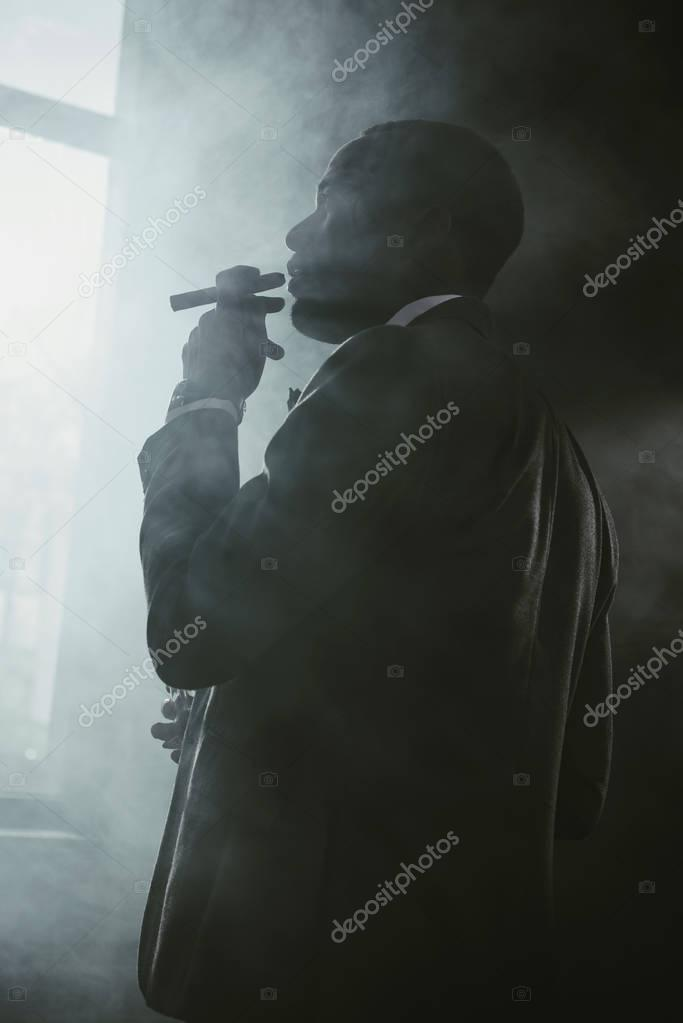 confident african american businessman in suit smoking cigar