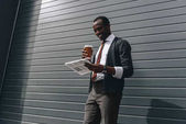Fotografie stylish african american businessman reading newspaper and holding coffee to go outdoors