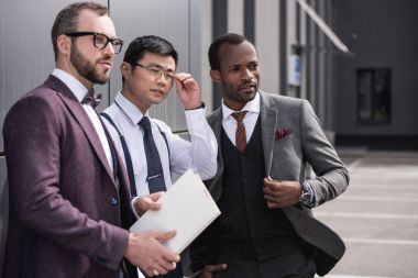portrait of confident multicultural business team standing near office and looking aside