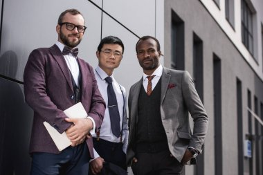 young stylish multiethnic businessmen in formalwear posing outdoors, business team meeting