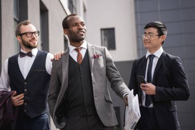young stylish multiethnic businessmen in formalwear walking outdoors, business team meeting