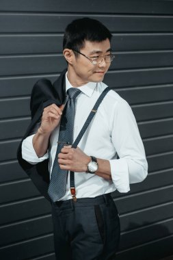Confident stylish asian businessman posing outdoors at wall