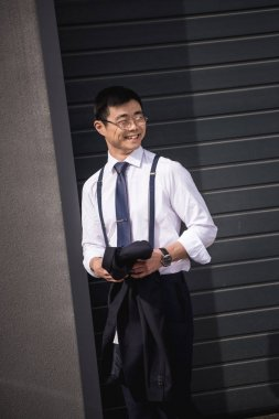 young stylish asian businessman in glasses standing outdoors