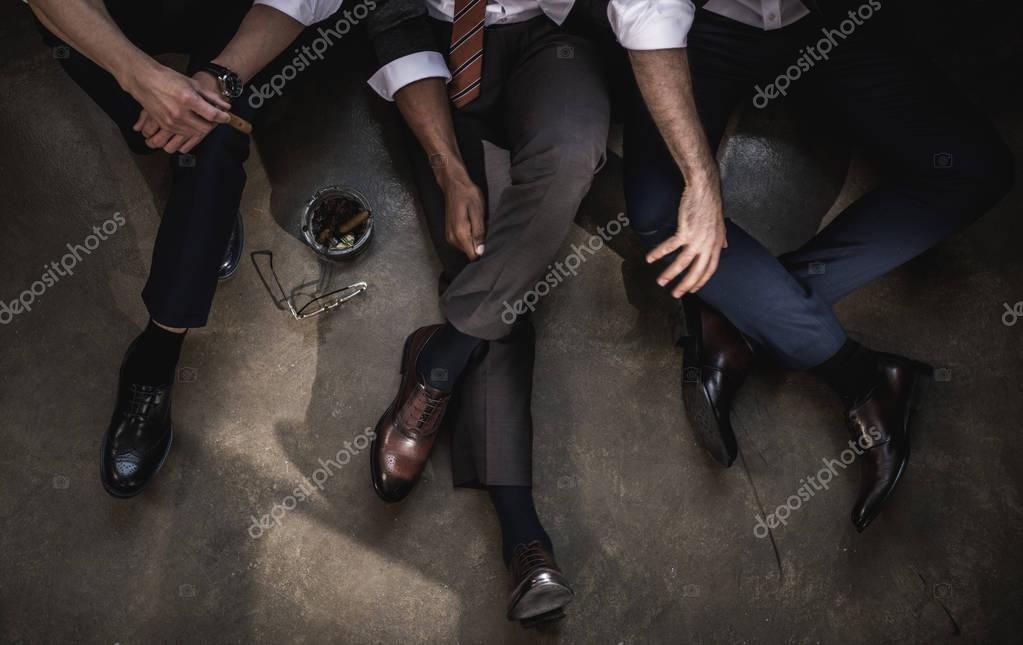 Cropped shot of group of businessmen sitting on floor together