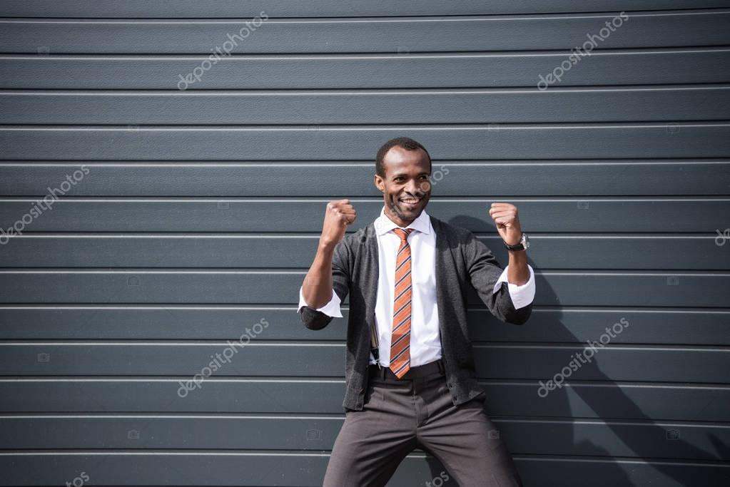 young happy african american businessman standing outdoors