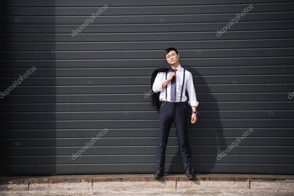 young confident asian businessman standing outdoors with copy space