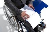 Fotografie Geschäftsmann in Rollstuhl mit leere Papierbögen