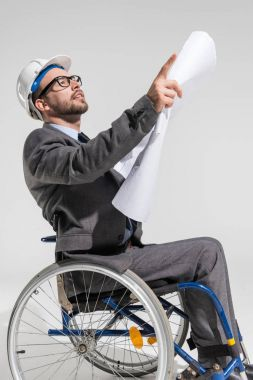 architect at wheelchair holding blueprint