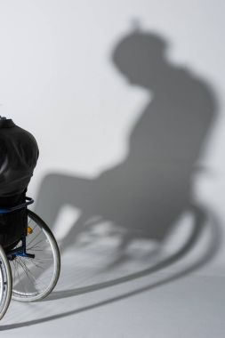 physically handicapped man in wheelchair with shadow