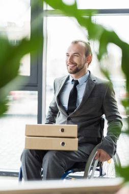 smiling physically handicapped businessman with folders