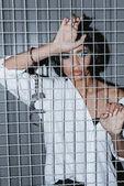 Frau im Hemd hinter Gitter