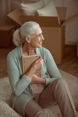 senior woman hugging photo in frame