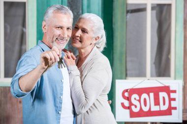 senior couple with new house keys